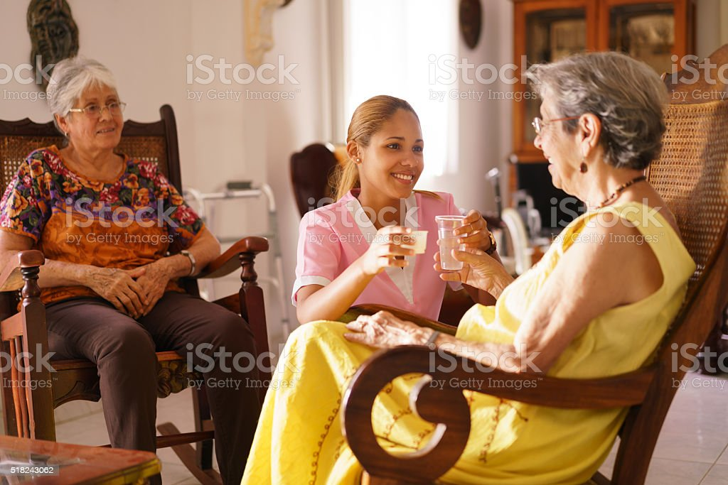 Hospice Nurse Serving Pill Medicine Water To Old Woman stock photo