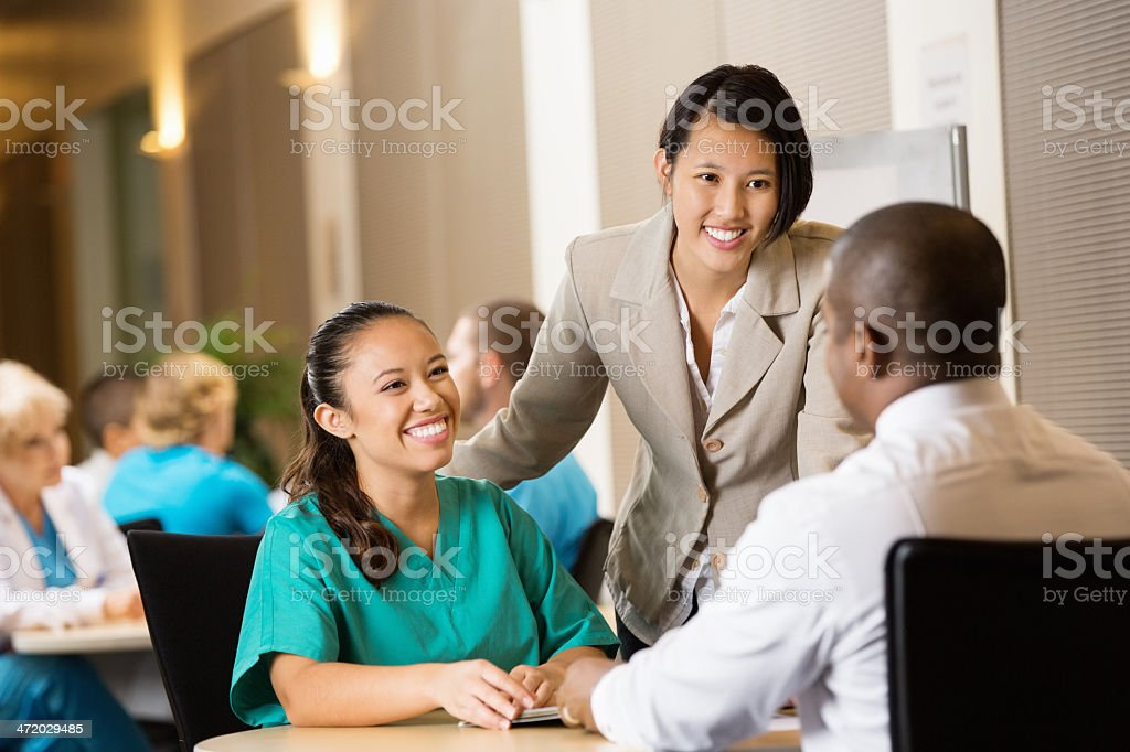 Hospital administrator interviewing nurse for potential employment stock photo