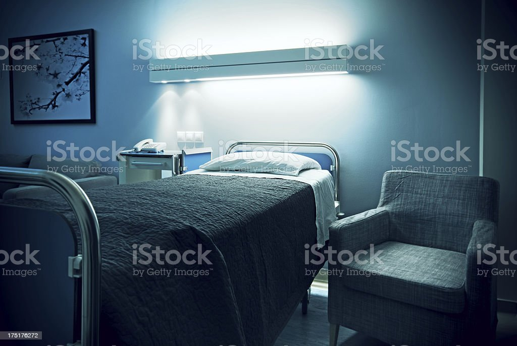 Hospital bed and visitor armchair stock photo