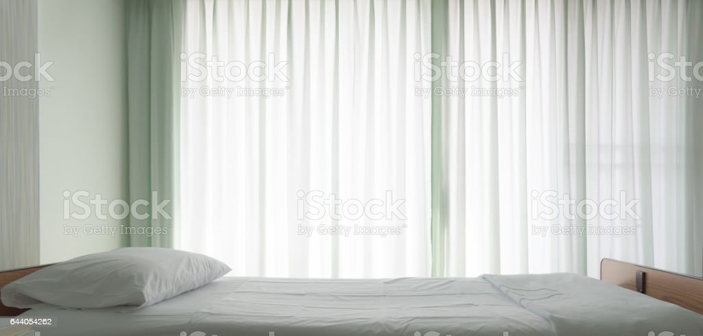 Hospital bed in patient room with sun light for background