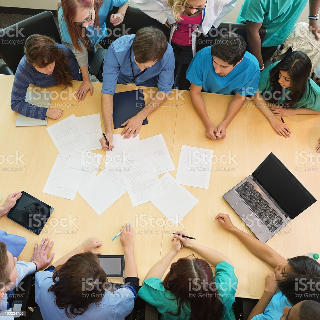 Hospital doctors and staff consulting about diagnosis; view from above stock photo
