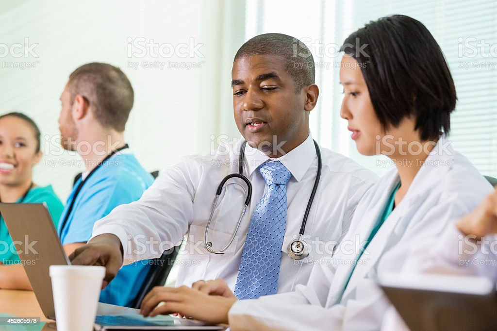 Hospital doctors working together on laptop during meeting royalty-free stock photo