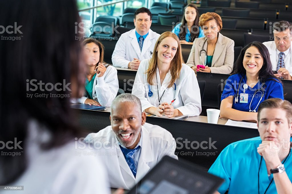 Hospital employees listening to speaker at healthcare conference training seminar stock photo
