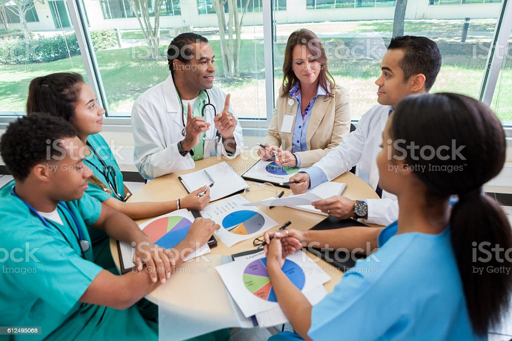 Hospital executive discuss strategy with hospital staff stock photo