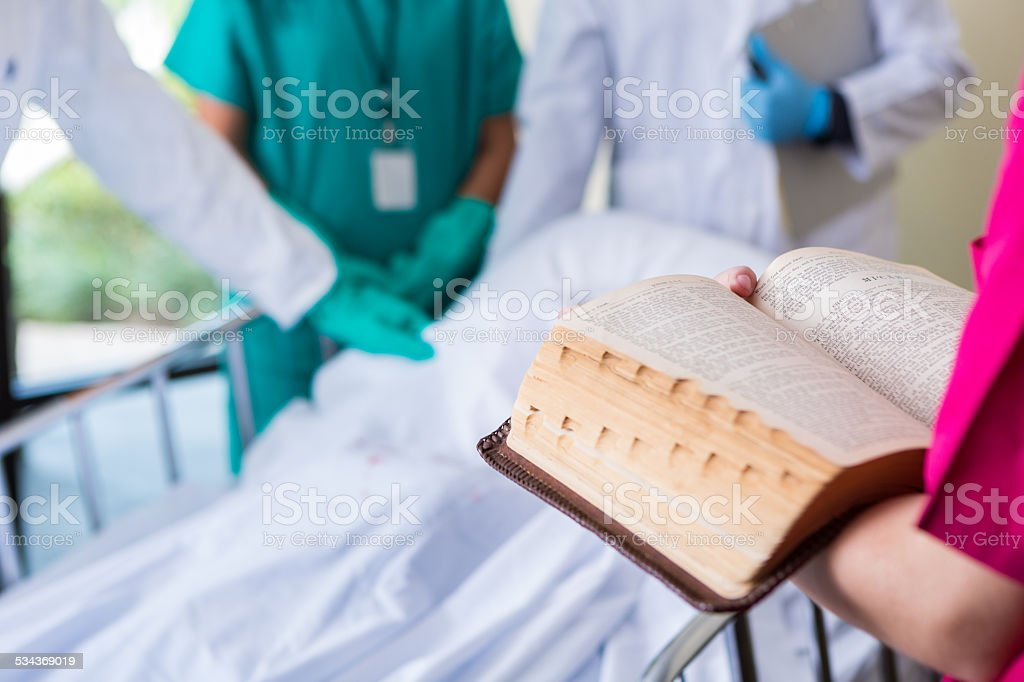 Hospital nurse or chaplain reading bible in patient room stock photo