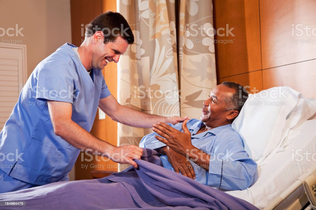 Hospital orderly assisting senior patient stock photo