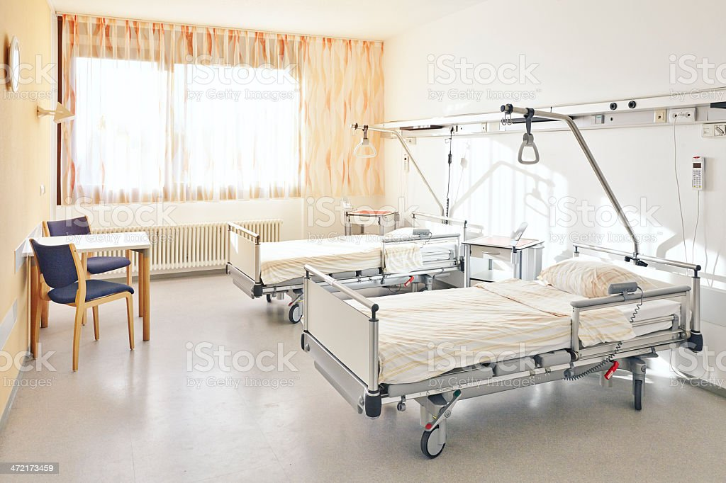 Hospital room with two beds and a table with two chairs stock photo