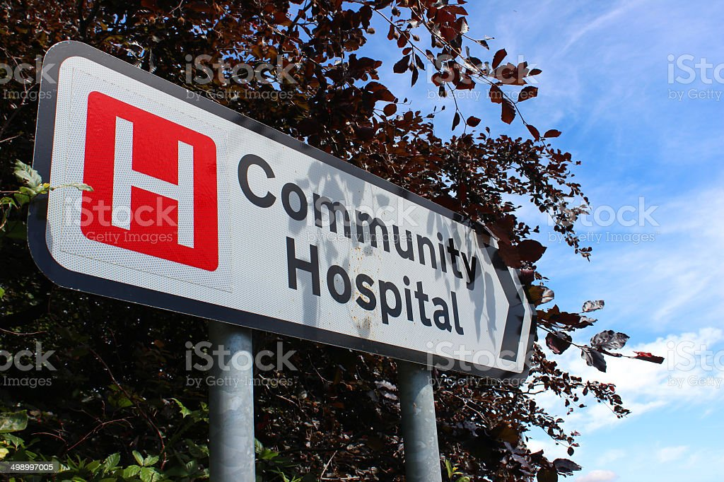 Hospital sign / white road sign / signpost pointing to Community Hospital stock photo