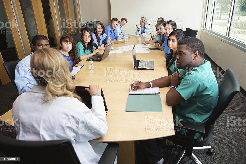 Hospital staff, doctors, & nurses having meeting in board room stock photo