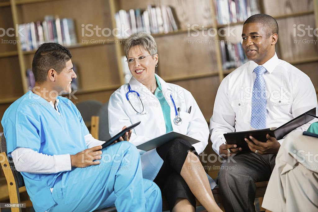 Hospital staff meeting with doctors, nurses, and administrators stock photo