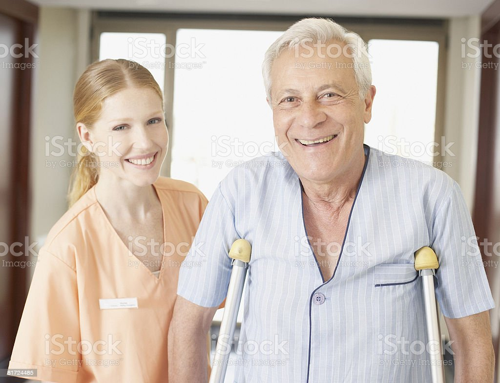 Hospital worker helping senior man in hospital corridor using crutches and smiling royalty-free stock photo