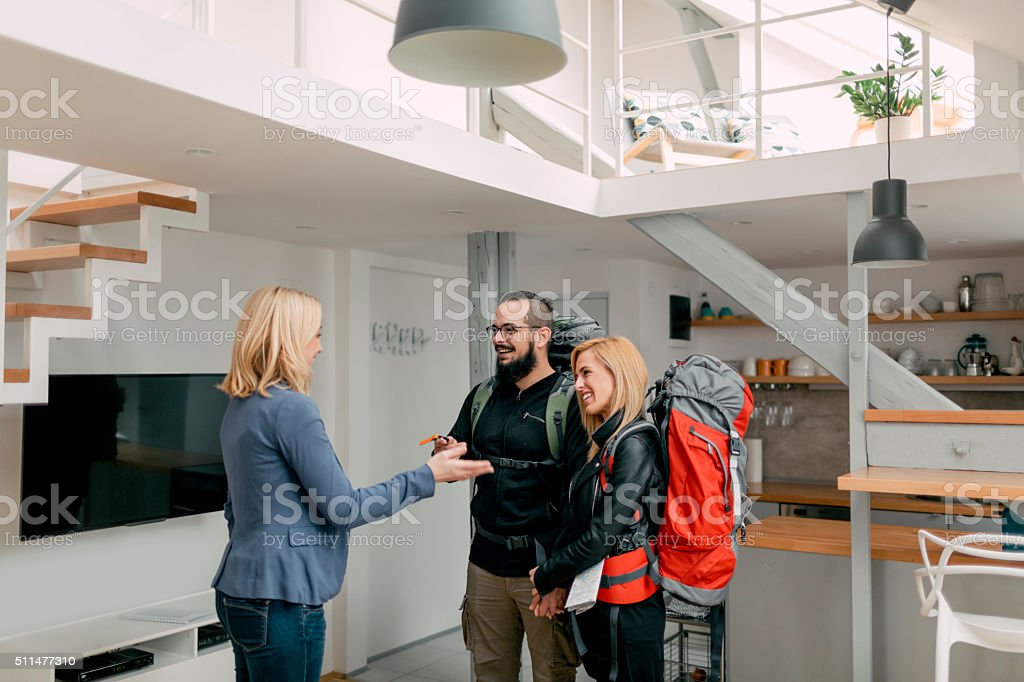 Host welcomes Backpackers In Her Apartment. stock photo