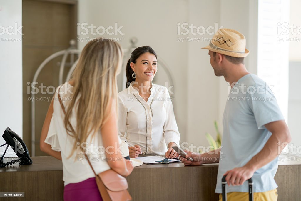 Hostess doing the check-in of a couple stock photo