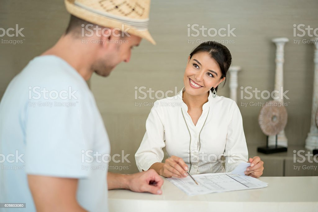 Hostess helping man do the check-in at a hotel stock photo