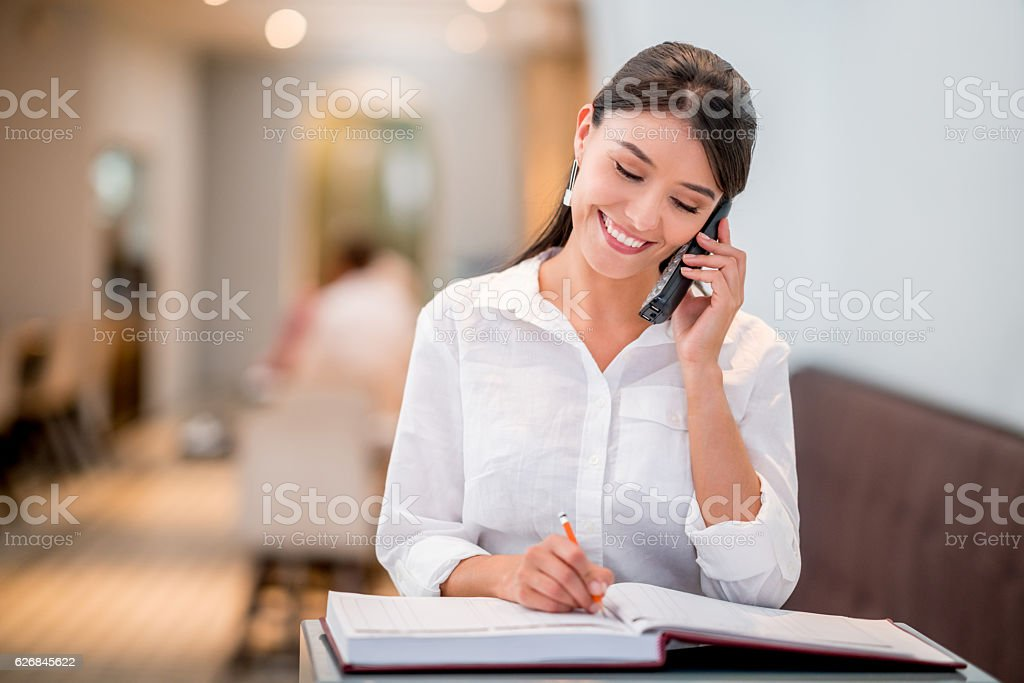 Hostess taking a reservation at a restaurant stock photo