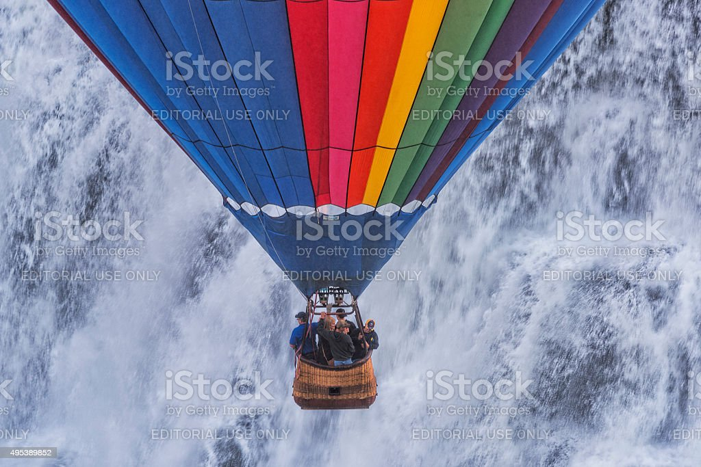 Hot Air Balloon Decending In Front Of A Waterfall stock photo