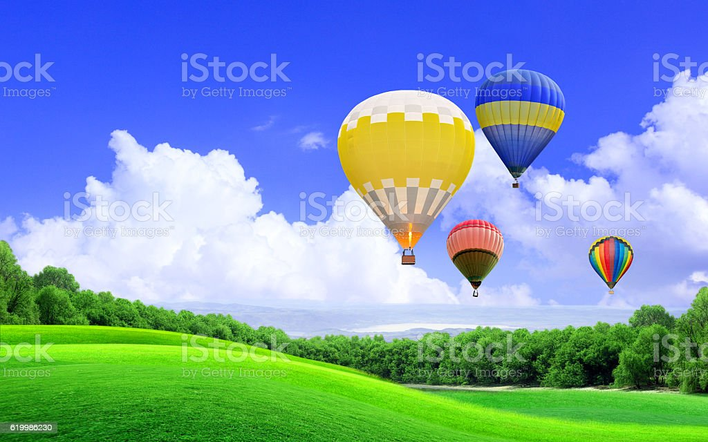 Hot air balloon floating in the sky over the hill stock photo