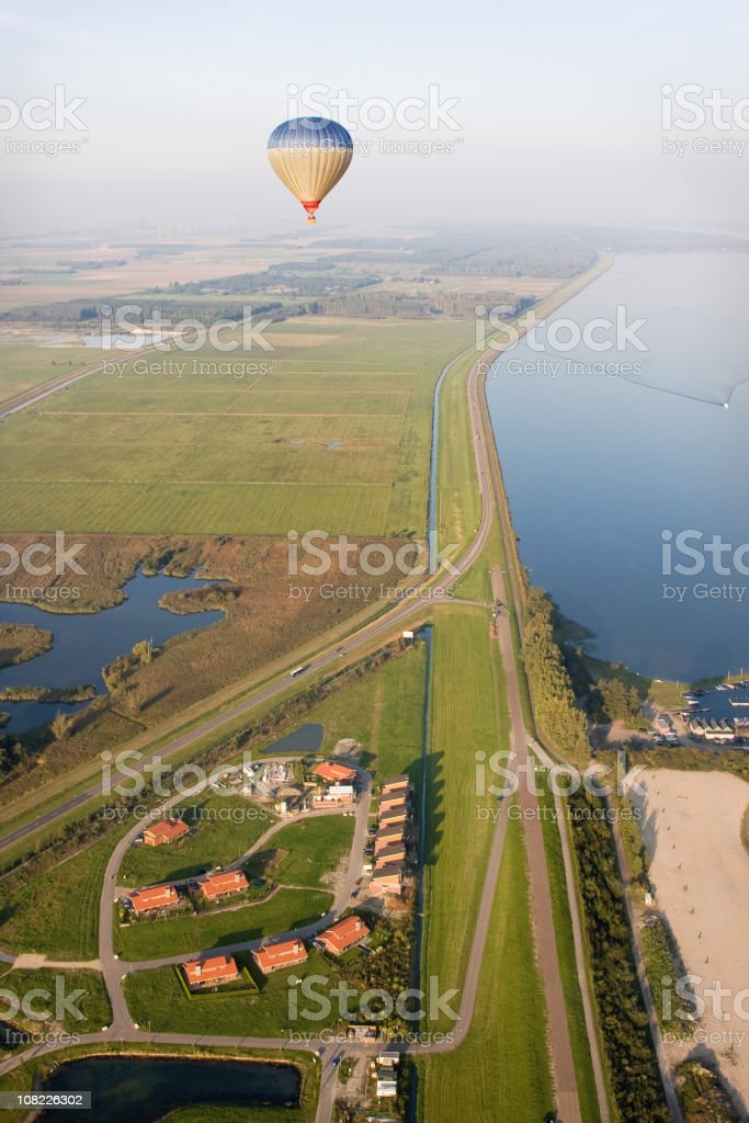 Hot Air Balloon floating over a scenic Dutch polder landscape royalty-free stock photo