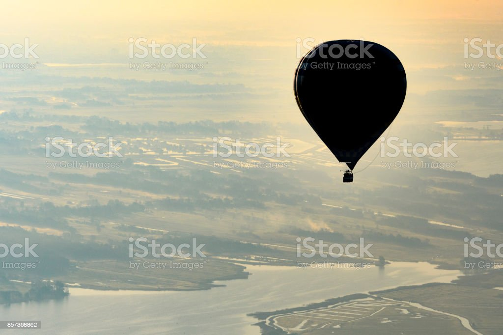 Hot air balloon flying in mid air during a beautiful morning in...
