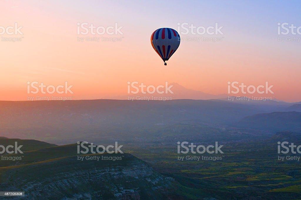 Montgolfière survolant paysage spectaculaire au lever du soleil, de la Cappadoce photo libre de droits