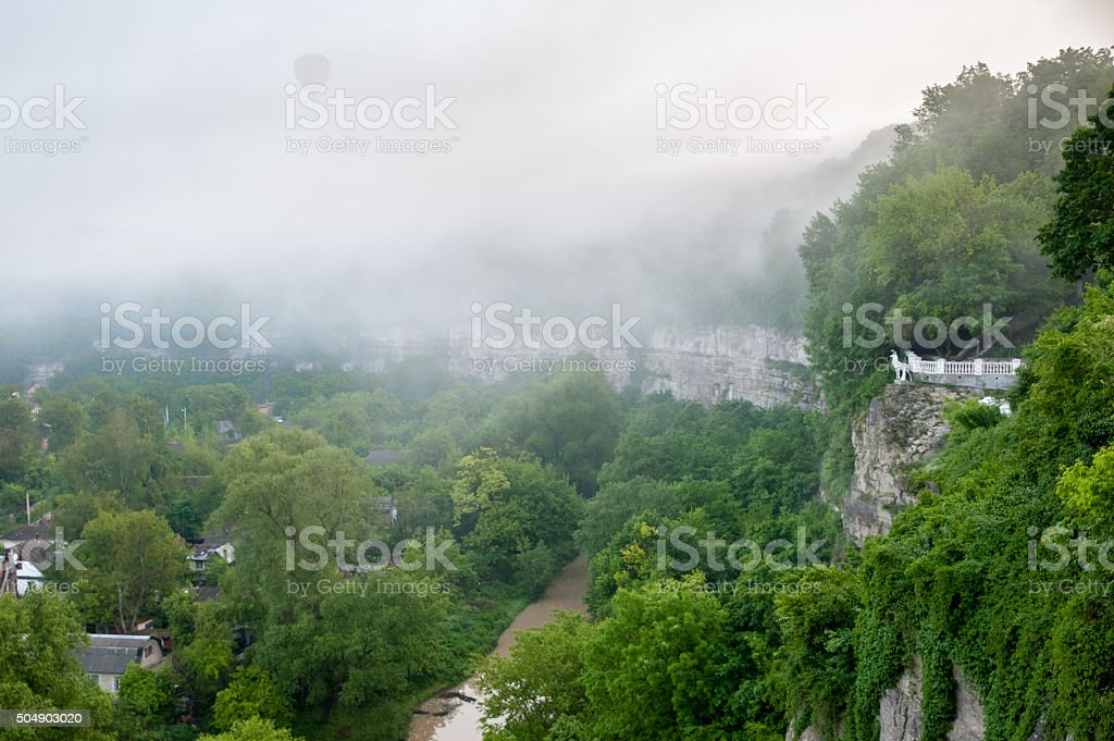 Hot air balloon flying over canyon in fog stock photo