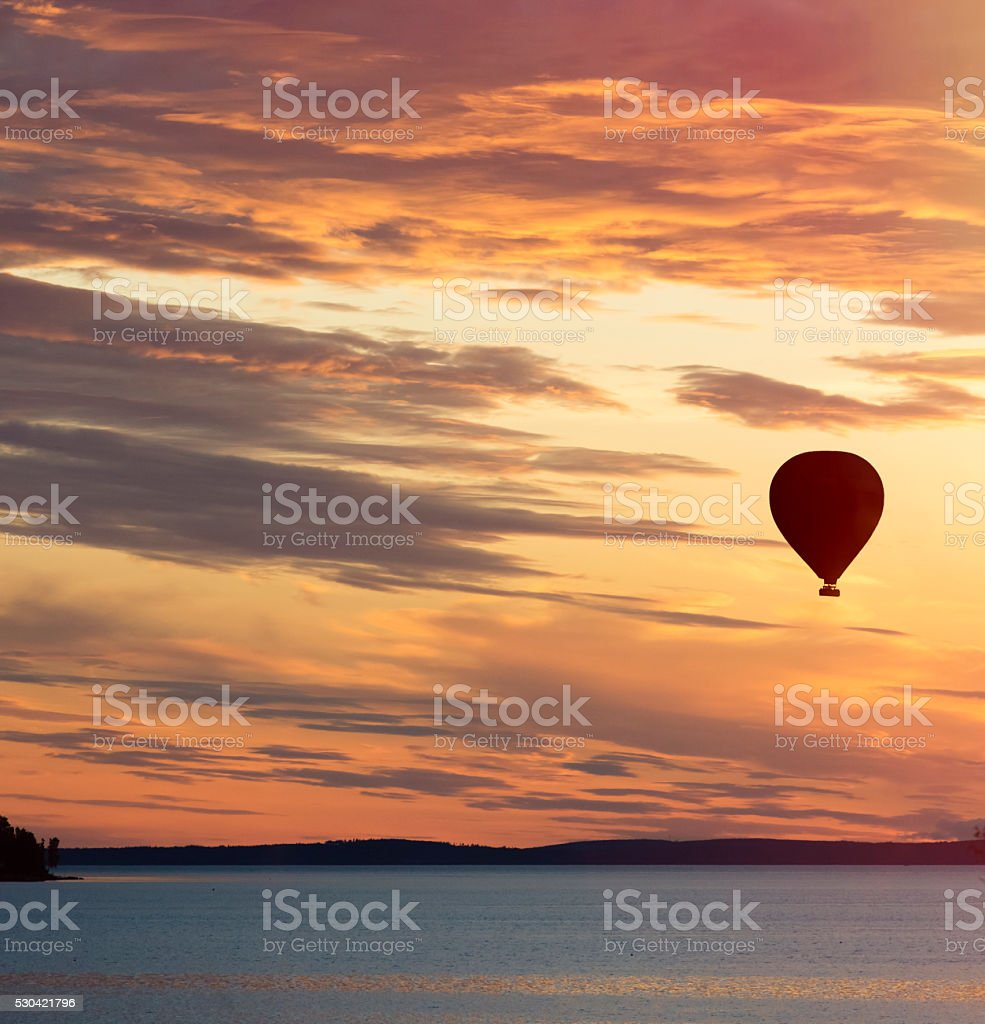 Hot air balloon flying over lake at sunset stock photo