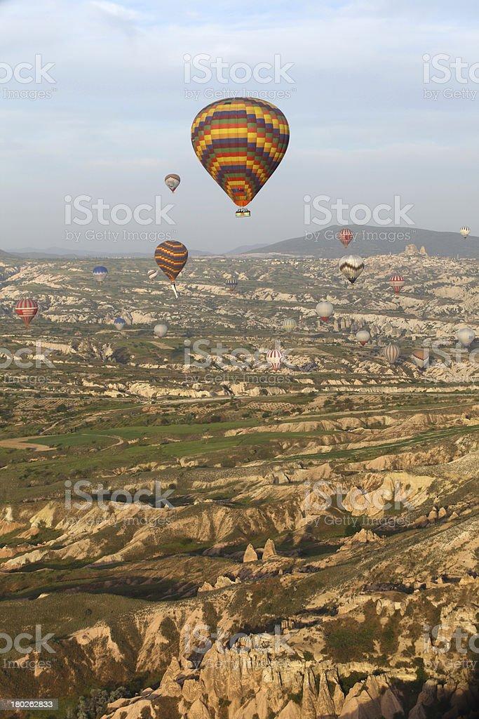 Hot air balloon flying over rock landscape at Cappadocia Turkey royalty-free stock photo