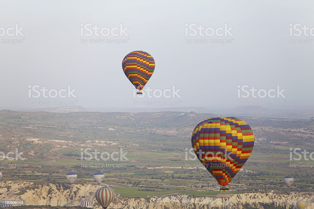 Hot air balloon flying over rock landscape at Cappadocia Turkey royalty-free stock photo