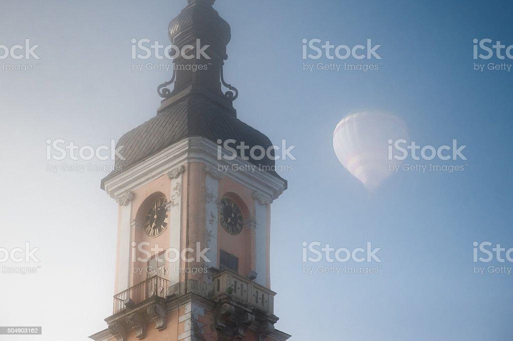 Hot air balloon flying over the church in fog stock photo