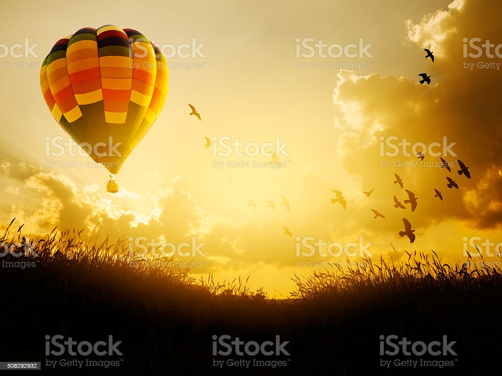 Hot air balloon flying with birds in sunset sky, stock photo
