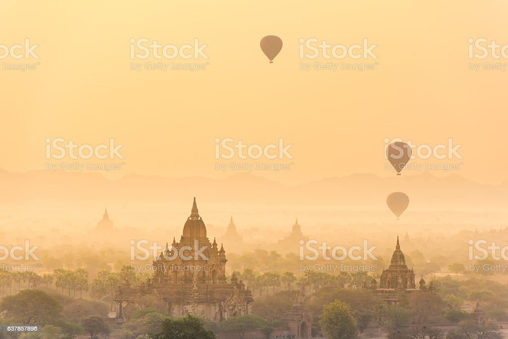 Hot air balloon over plain of Bagan in misty morning stock photo