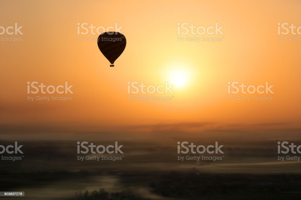 Hot air balloon silhouetted in the  early morning sun during  flight, with foggy patches in the Valley of the Kings, Egypt, Africa stock photo