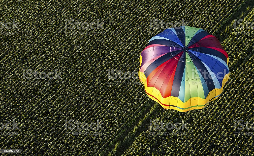 Hot air balloon/Parachute flying over a field royalty-free stock photo
