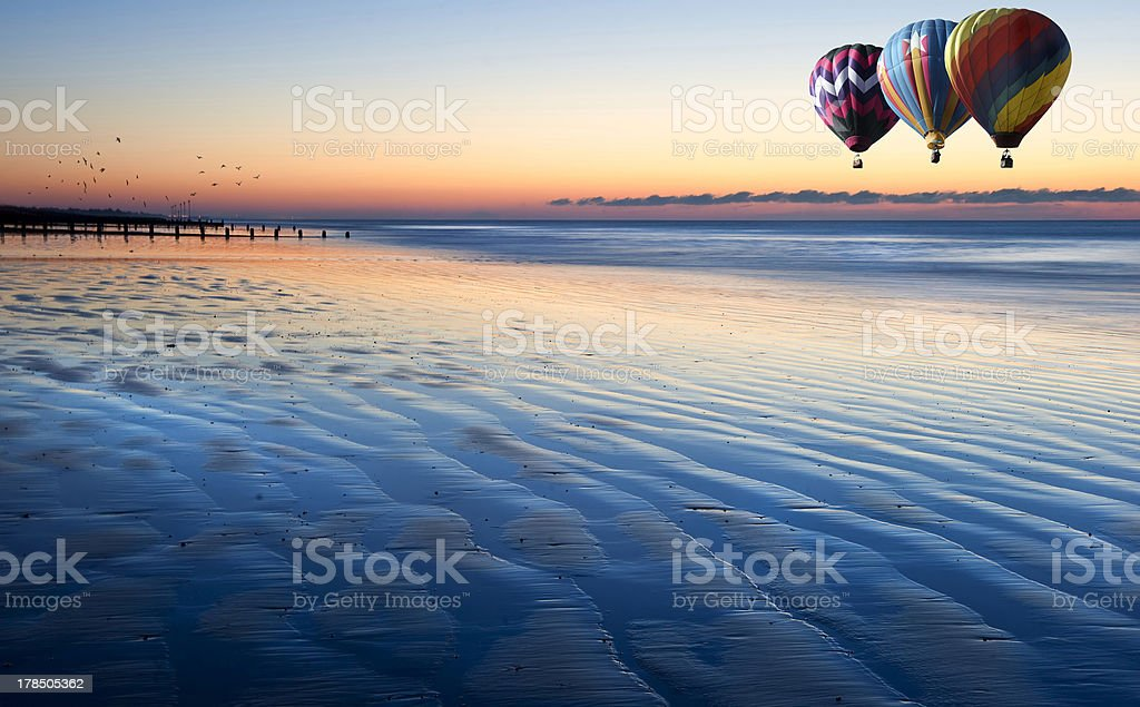 Hot air balloons over beautiful low tide beach vibrant sunrise royalty-free stock photo