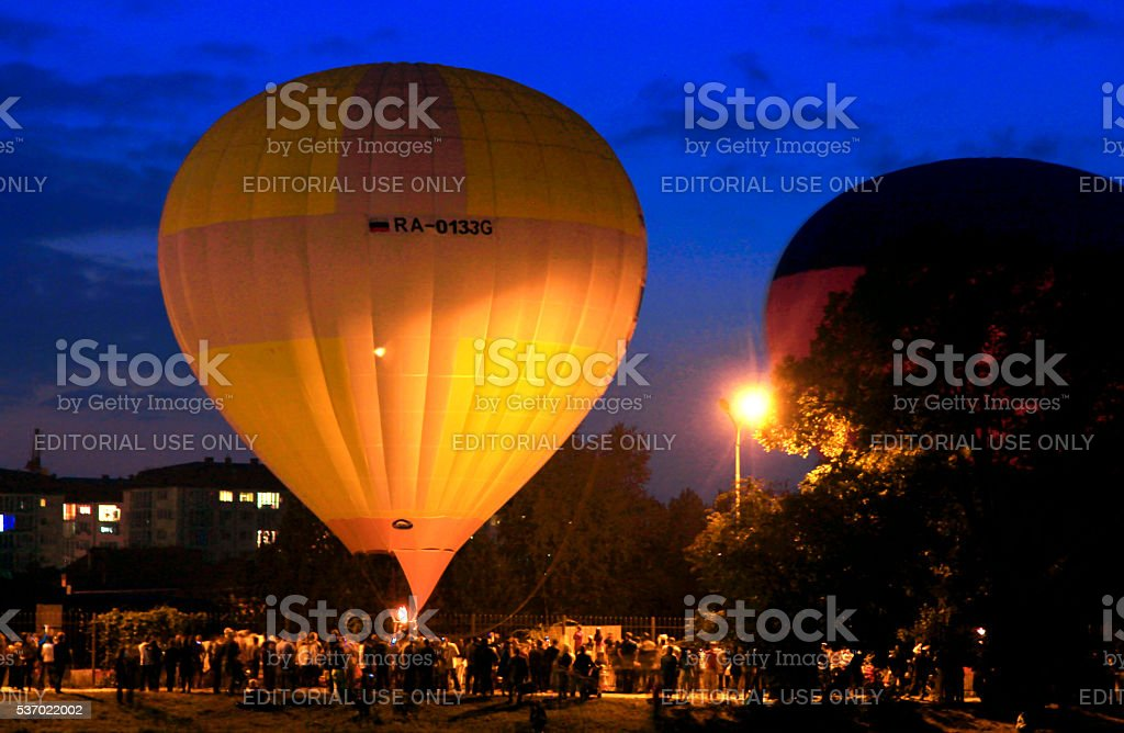 Hot air baloons startung to fly in the evening sky stock photo