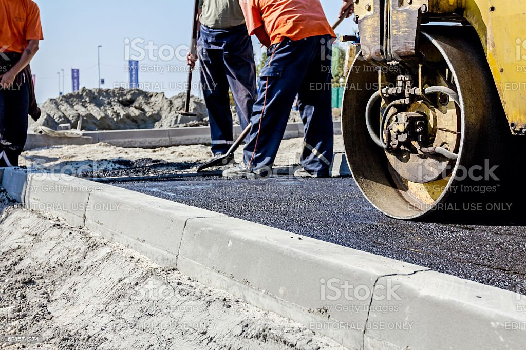 Hot asphalt is spreading with steamroller during road works stock photo
