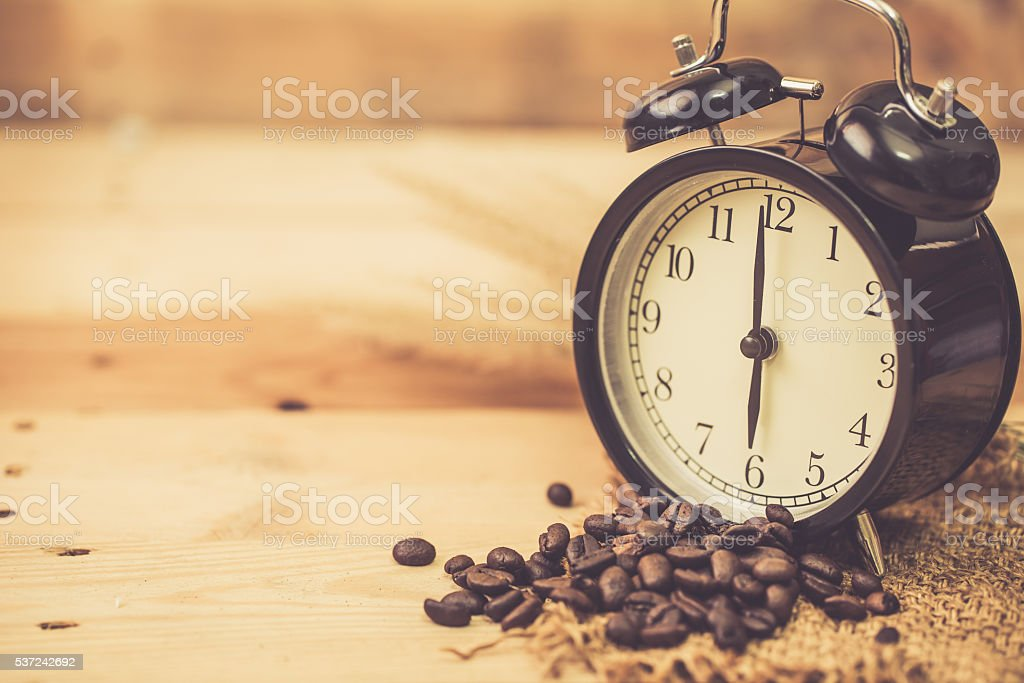 hot black coffee bean with smoke and clock on wood. stock photo