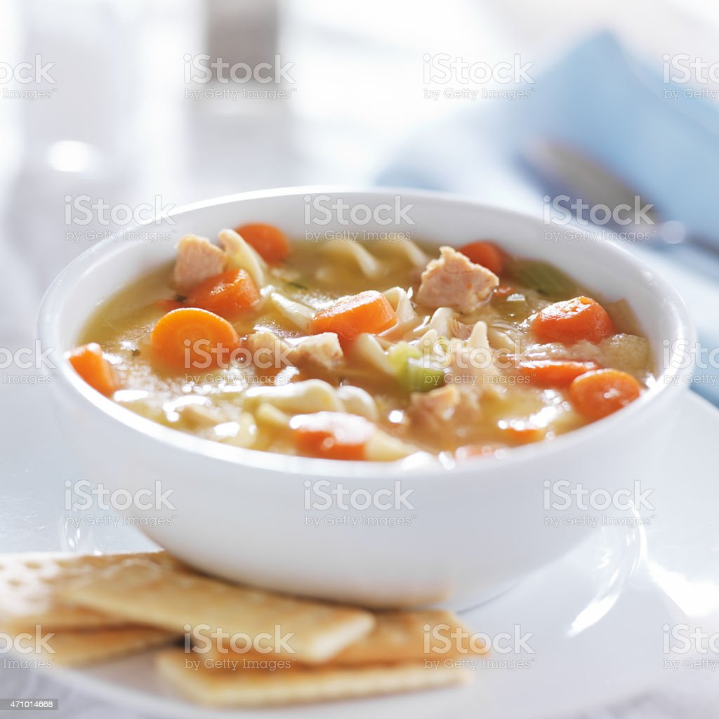 hot bowl of chicken noodle soup on table stock photo