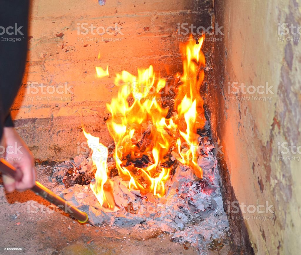 hot burning flaming fire being poked stock photo