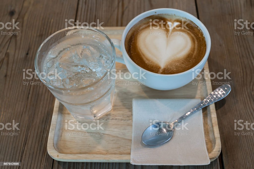 hot cappuccino coffee with ice water on wood table stock photo