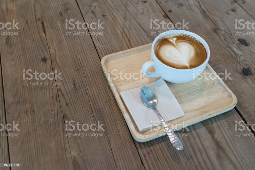 hot cappuccino coffee with napkin and spoon on wooden table stock photo