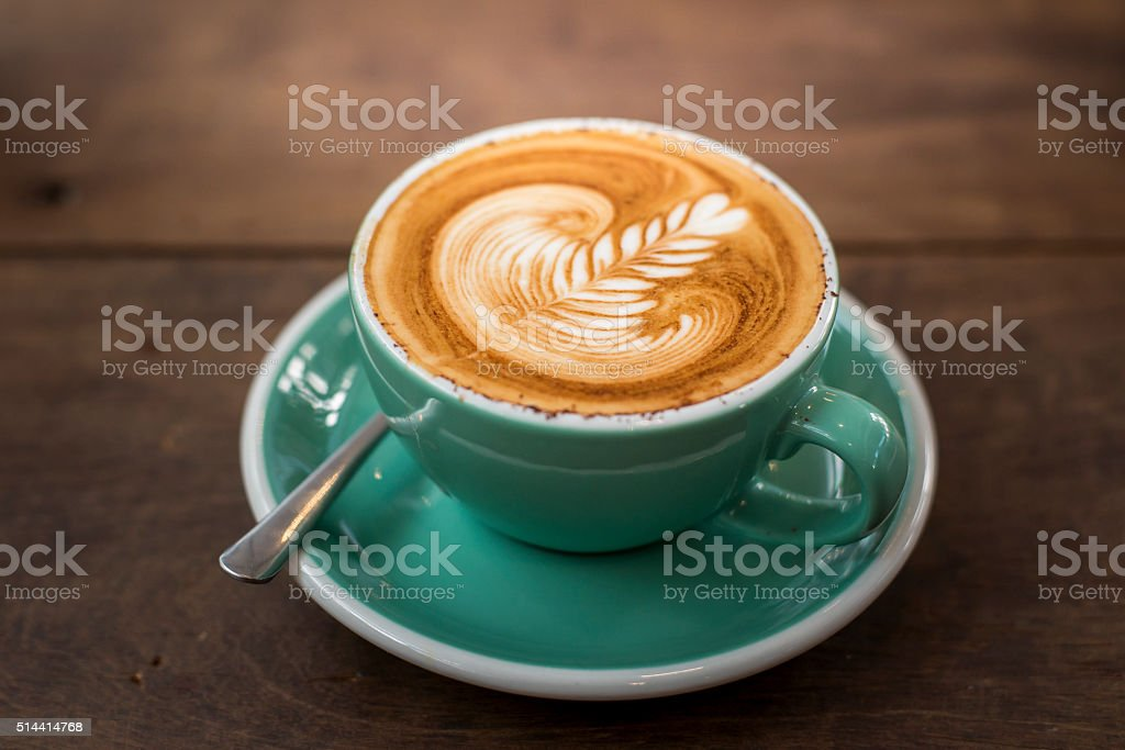 hot cappuccino with latte art on wood background stock photo