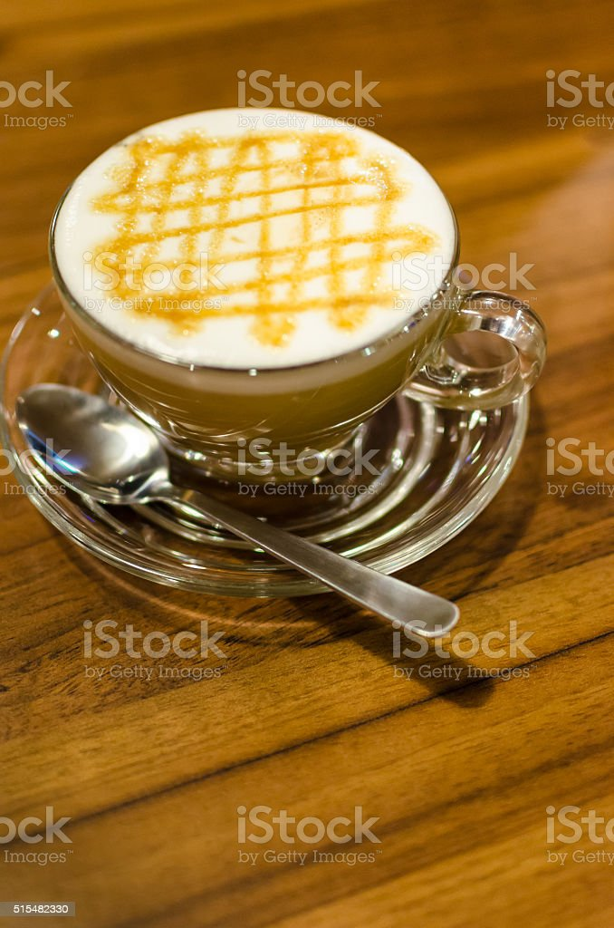 Hot caramel coffee macchiato and white milk foam in glass stock photo