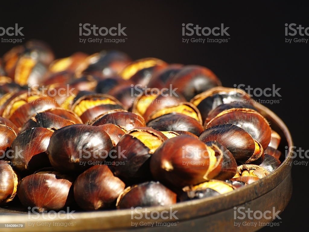 Hot chestnuts on black background. royalty-free stock photo