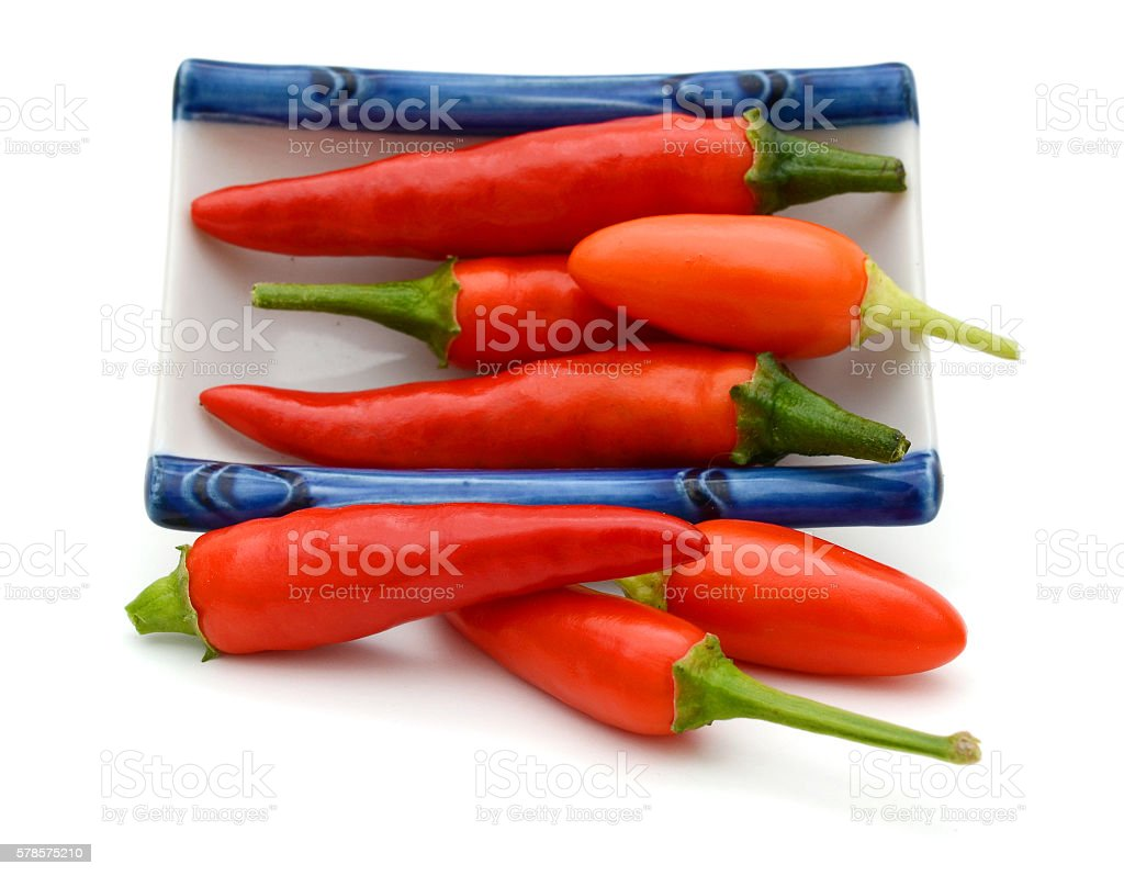hot chili peppers on white plate stock photo