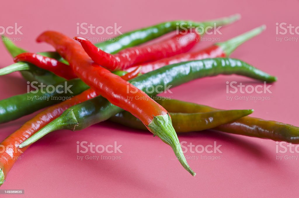 Hot chilli peppers on pink background royalty-free stock photo
