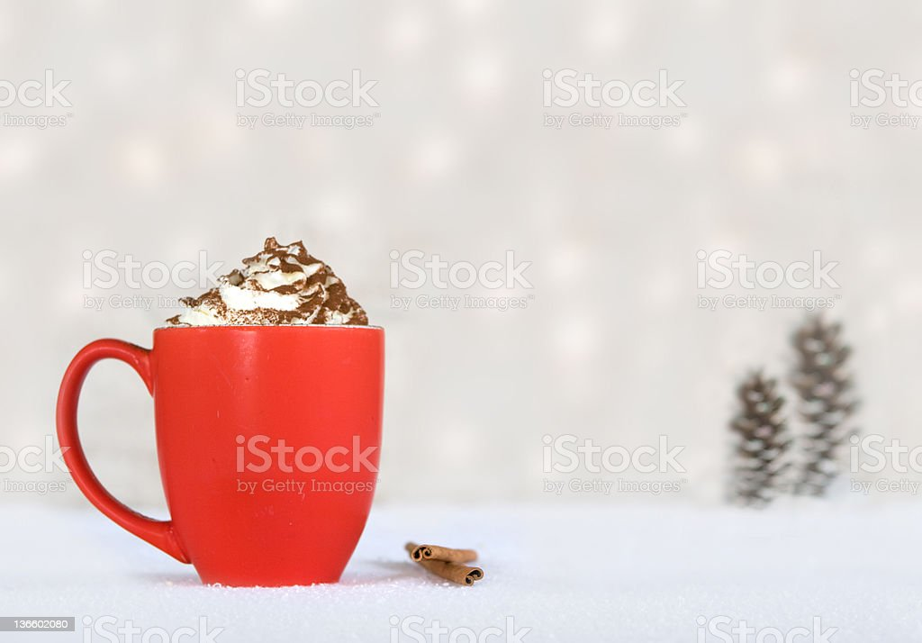 Hot cocoa in a red mug against a white, snowy backdrop royalty-free stock photo