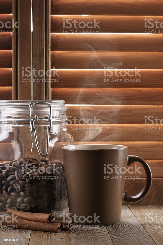 Hot coffee against shutters stock photo