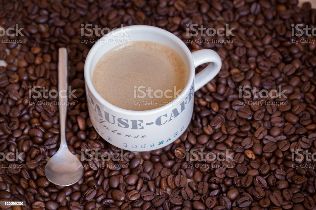 Hot and steamy coffee mug on a wood table with a muffin