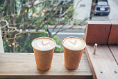 Hot coffee heart shape in paper cup on table terrace